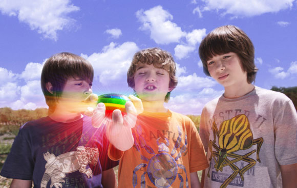 """Lug (REBEL RODRIGUEZ, left) and Laser (LEO HOWARD, right) watch as Loogie (TREVOR GAGNON) closes his eyes to make a wish on the Rainbow Rock in Warner Bros. Pictures' magical fantasy adventure """"Shorts."""" Photo courtesy of Warner Bros. Pictures"""