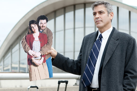 Ryan Bingham (George Clooney, far right) holds up a cardboard photo of his sister Julie (Melanie Lynskey, far left) and her fiancé Jim (Danny McBride, near left) in the dramatic comedy UP IN THE AIR, a Paramount Pictures release. Photo Credit: Dale Robinette. Copyright © 2009 DW STUDIOS L.L.C. and COLD SPRING PICTURES. All Rights Reserved.